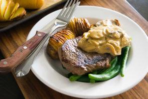 Thick Cut Porterhouse, Mushroom Sauce, Hassleback Potatoes & Buttered Beans